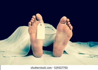 The dead woman's body with blank tag on feet under white cloth in a morgue - retro style