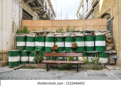Dead zone at Nicosia. Barricades in Nicosia, Lefkosia, Cyprus. Blockhouse, checkpoint, sentry post. Painted barrels, plants, bench. Abandoned houses.
