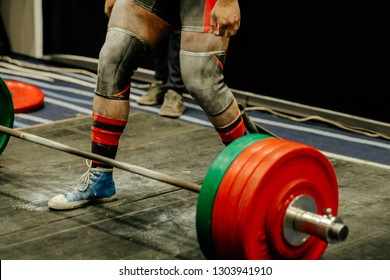 deadlift man athlete legs in chalk gym and knee sleeves protection