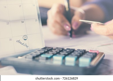 deadline calendar note with blur background of business woman hand writing on paper  counting on credit card with blur calculator in foreground