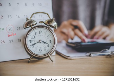 deadline calendar for taxes payment with alarm clock on desk and blur business woman calculating in background