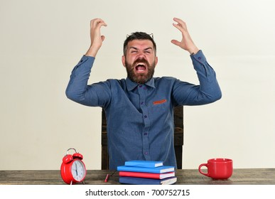Deadline and hard work concept. Man with beard and glasses on head isolated on white background. Guy screams or sneezes and sits at wooden table. Cup and retro clock with red and blue books on table