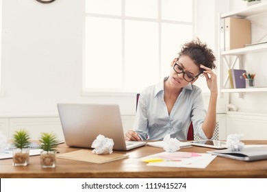 Deadline stress concept - sad african-american business woman sitting at desktop in office and holding hand on head. Hard working day, copy space