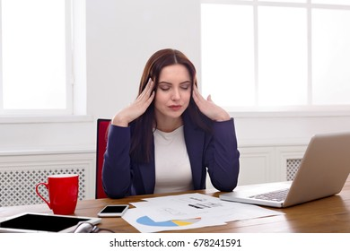 Deadline stress concept - sad business woman sitting at desktop in office and holding hands on head. Hard working day.