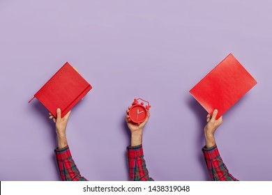 Deadline and studying concept. Set of male hands carries red notepad, textbook and alarm clock, shows time gone, prepares for exam. Schedule and regime. Time for break. Back to school. Copy space