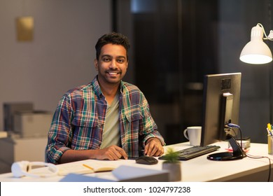 deadline, technology and people concept - happy creative man with tablet pc computer working at night office