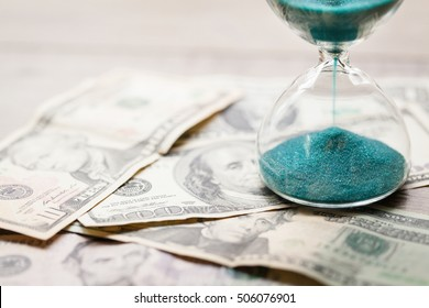 Deadline and time is money concept with hourglass and US Bills currency (One, five, ten, twenty, and hundred dollars). Sandglass