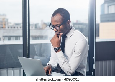 Deadline today. Pensive elegant smart african businessman in glasses is sitting in office while holding laptop on knees and looking at monitor with concentration. He is touching his chin thoughtfully