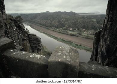 Deadpan dark stone bridge Bastei in Saxon Switzerland with the rainy mist over the river Elbe, National park Saxon Switzerland.