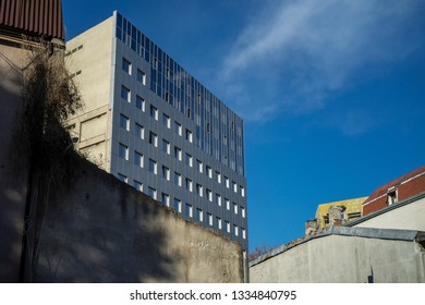Deadpan image of juxtaposed buildings old and new, residential and business against the blue spring sky.