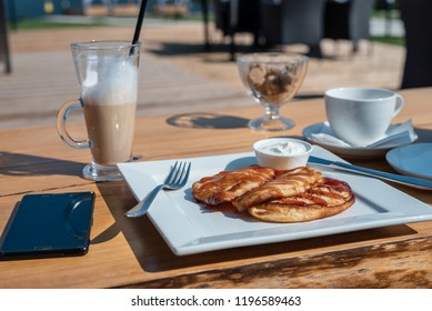 Deadpan image of pancake with honey, sour cream on wooden table with fork, spoon, smartphone and cup of tea.