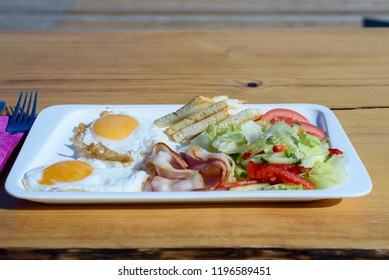 Deadpan photo of village Breakfast with eggs, bacon and vegetable salad.