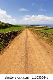 A dead-straight track leads through a hilly landscape to the sea, on the edge of natural stone walls, great depth, sky with some clouds - Location: Azores, Sao Jorge Island