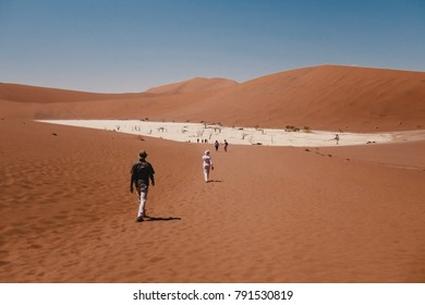 Deadvlei, Namibia - December 22, 2017: Tourists walk  in the dunes toward the Deadvlei, Sossusvlei. Namibia