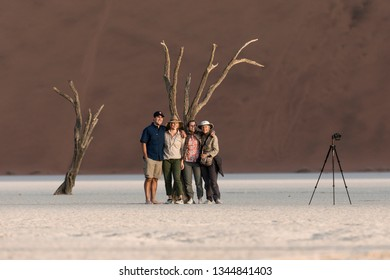 Deadvlei, Sossusvlei, Naukluft National Park, Namibia : July 23, 2017: A family poses in Deadvlei for a photo. Tourist numbers are swelling in the park causing the ancient trees to be broken.