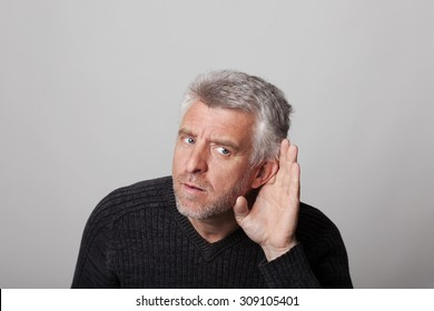 deaf aged man listens with his hand to his ear