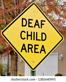 A deaf child warning sign shows.