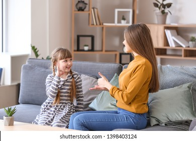 Deaf mute mother with daughter using sign language at home