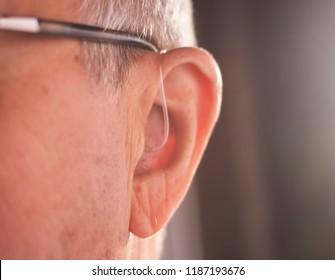 Deaf senior citizen man wearing modern digital high technology hearing aid in ear.