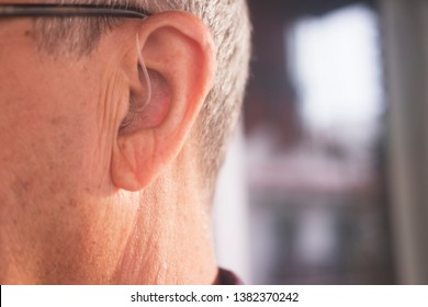 Deaf senior citizen man wearing modern digital high technology hearing aid in ear.
