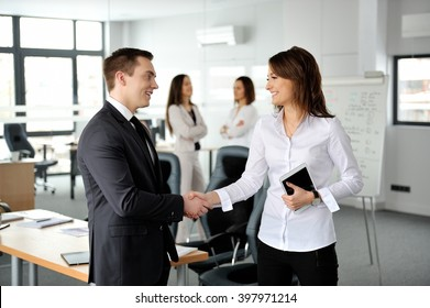 It's a deal! Business people handshaking. Their colleagues on a background.