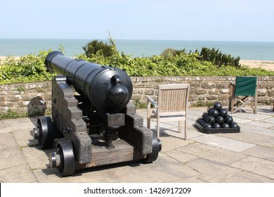 Deal, England - 7 May 2019:  A cannon overlooking the sea with some cannon balls secured nearby it at Walmer Castle in Deal. Travel destinations in Europe.  Summer Travels England 2019
