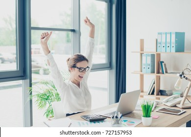 Deal, income, profit, feminity, triumph, victory, happiness concept. A dream of cheerful excited stylish lady leader came true! she is sitting at her light modern work station, celebrating