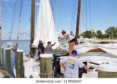 Deal Island, Maryland, USA - September, 2, 2018: Boaters make repairs on a sail prior to the annual Deal Island Skipjack Races and Festival.