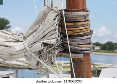 Deal Island, Maryland, USA - September, 2, 2018: A view of skipjack sailing boat's mast rings and folded sails.