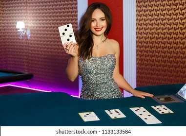 Dealer in the casino at the poker table. The dealer gives out cards.Girl in casino