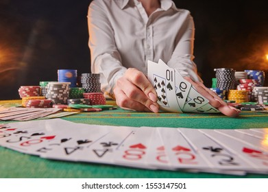 dealer in a casino raises a combination of street poker, on the background with chips. money, poker, success