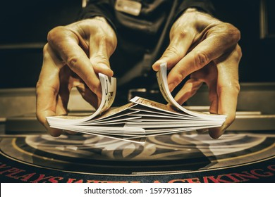 Dealer or croupier shuffles poker cards in a casino on the background of a table, chips,. Concept of poker game, game business