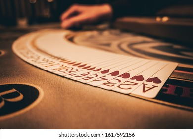 Dealer or croupier shuffles poker cards in a casino on the background of a table, chips,. Concept of poker game, game business.