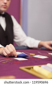 Dealer distributing cards in a casino while sitting at table