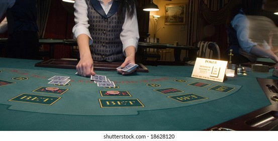 dealer handling and passing out playing cards at a poker table in casino