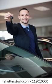 Dealer holding car keys in a dealership