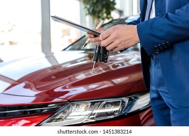 Dealer holding keys from new car close up