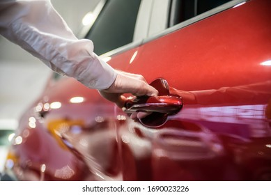 Dealer opens the red car in a car dealership