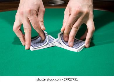 Dealer shuffle cards in casino over green felt