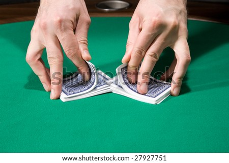 Dealer shuffle cards in casino over green felt