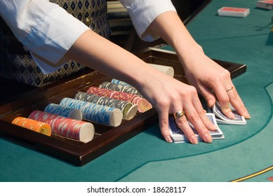 dealer shuffling playing cards at a poker table in casino