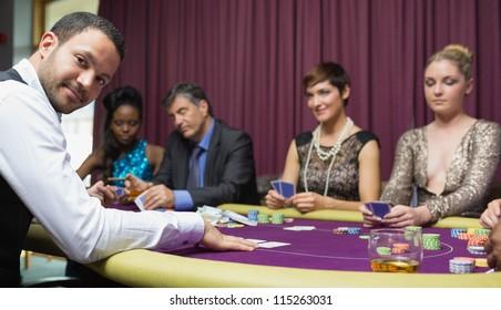Dealer smiling at poker game in casino