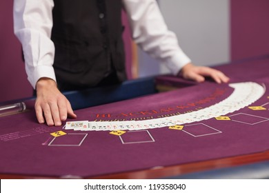 Dealer standing before a table in a casino and dealing out cards