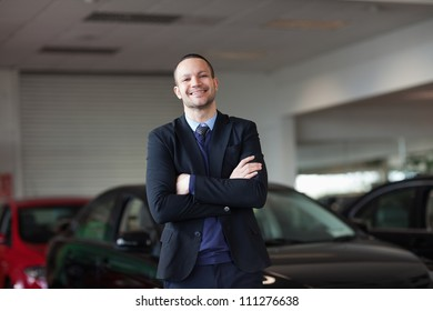 Dealer standing in front of a car in a garage
