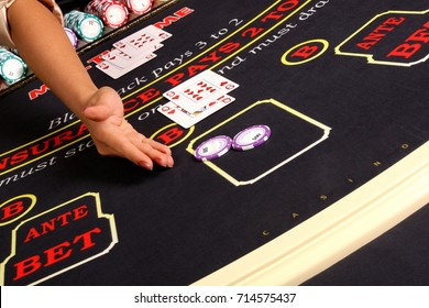 The dealer's hand points to the game chips at the blackjack table in the casino