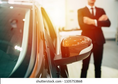 Dealership concept, focus on car on background salesman in suit with crossed arms