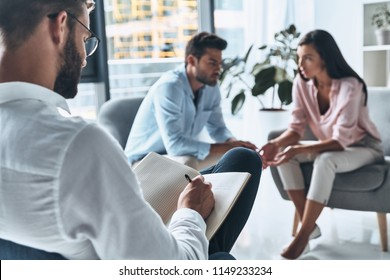 Dealing with conflict. Young married couple talking while sitting on the therapy session with psychologist