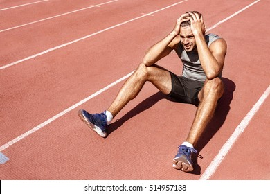 Dealing with the loss. Young male athlete looking upset and disappointed after losing the race sitting on the racetrack with his hands to his head copyspace
