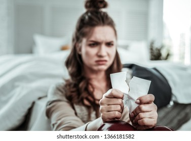 Dealing with memories. An upset woman breaking the photo of her ex