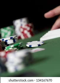 Dealing Poker Scene. a hand grabs for some cards in the distance of a poker table scene. low angle